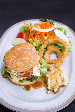 deep fry: Selective focus of hamburger with ham and cheese, mash potato, deep fry onion ring and salad