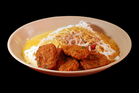 pla: Isolated selective focus of Thai fish cake with rice noodle and curry on black background, Thod Mun Pla