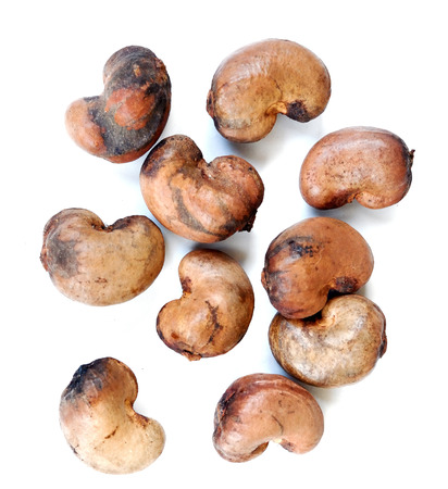 Isolated Roast cashew nuts in shell pile on white background, selective focus Stock Photo