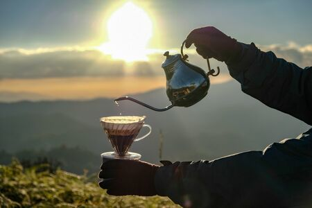 Man hand pouring filter coffee drip with outdoor natural