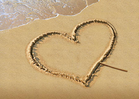 couple drawing a heart on wet golden beach sand