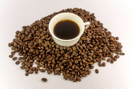 white cup full coffee on the coffee beans