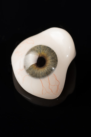 ocular: Glass eye prosthetic or Ocular prosthesis with reflection on black