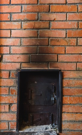 iron stove in the Russian bath lined with red brick Stock Photo