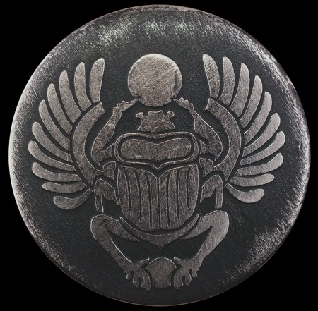 Scarabaeus carved in silver coin isolated on black background, an Anciant egyptian scarab beetle