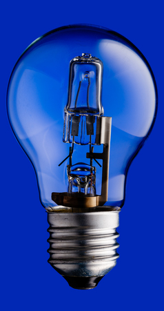 Realistic photo image of a halogen light bulb isolated on a blue background and with a clipping path Stock Photo