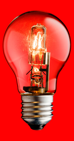 Realistic photo image of a turned on halogen light bulb isolated on a red background and with a clipping path