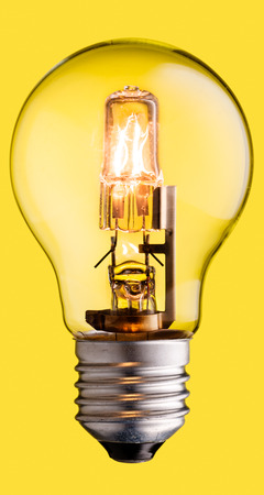 inteligent: Realistic photo image of a turned on halogen light bulb isolated on a yellow background and with a clipping path