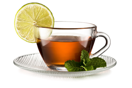Glass cup of black tea with lemon slice and mint leaves isolated on white background