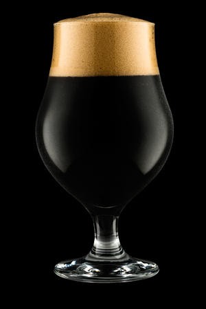 Glass of dark beer isolated on black background with clipping path