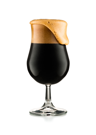 Glass of dark beer with overflowing head, isolated on white background Stok Fotoğraf