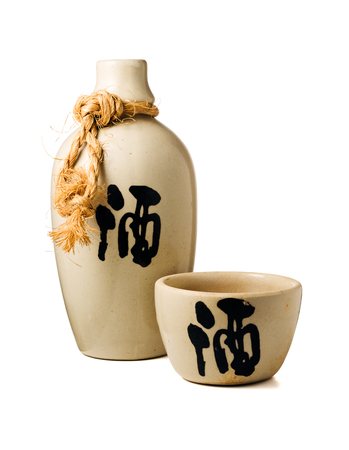 Sake bottle and cup, with the ideogram for liquor on both, isolated on white background with clipping path