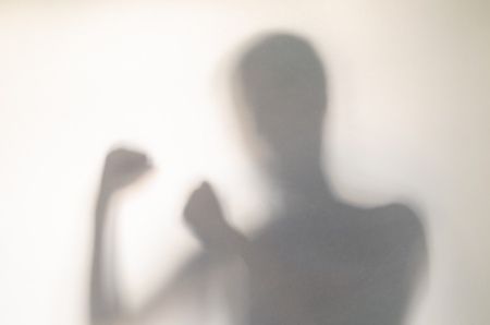 Man in fighting pose behind curtain. Hands and blurry human figure abstraction.
