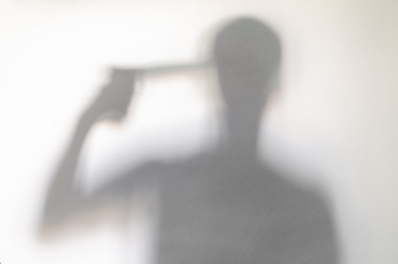 Suicidal man holding a gun at his head behind curtain. Blurry human figure abstraction. Stock Photo