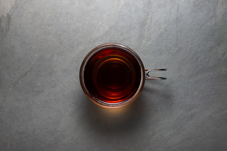 Top view photo of a black tea cup over a stone background and clipping path