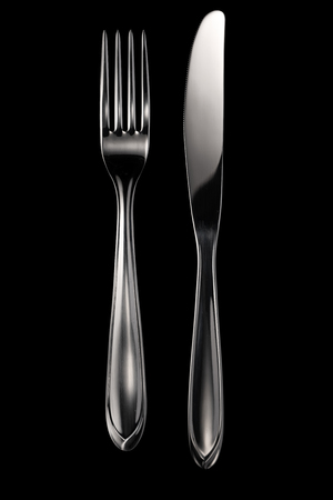 Knife and fork isolated on black background with clipping path