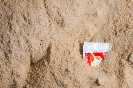 Disposable plastic packing piece on sand background. Plastic pollution affecting marine ecology. Environment concept.
