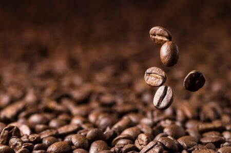 Brown Roasted Coffee Beans Falling on Pile with Copy Space on the Left 版權商用圖片