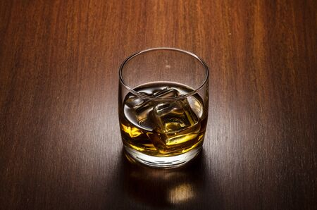 Glass of whiskey on the rocks, positioned on the  center of the composition, isolated on wooden background and with clipping path