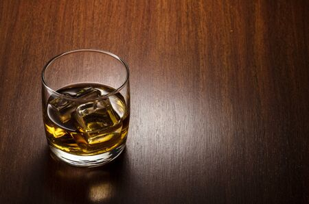 Glass of whiskey on the rocks, positioned on the left side of the composition, isolated on wooden background and with clipping path