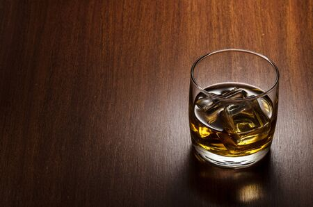 Glass of whiskey on the rocks, positioned on the right side of the composition, isolated on wooden background and with clipping path