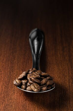 Close-up of roasted coffee beans on a spoon, isolated over a wooden surface background with clipping paths
