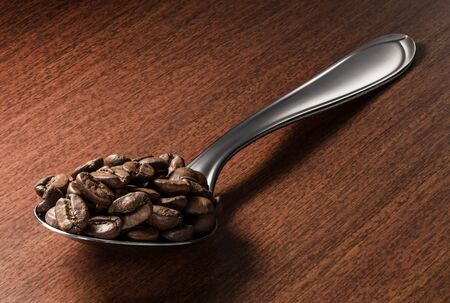 Close-up of roasted coffee beans on a spoon, isolated over a wooden surface background with clipping path
