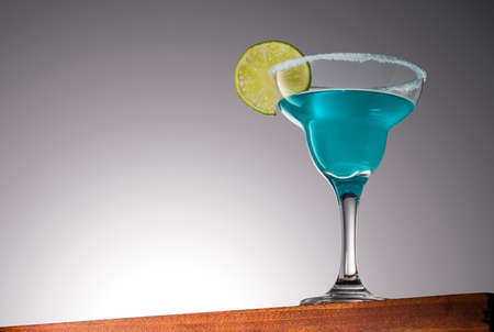 Blue Margarita Cocktail on a Wooden Surface With Gradient Background