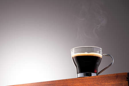 Close up photo of a coffee cup on a Wooden Surface and Gradient Background