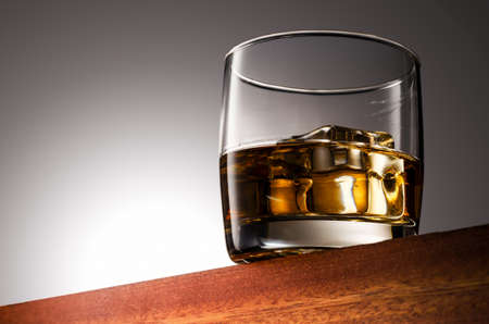 Glass of whiskey on the rocks on a Wooden Surface With Gradient Background 版權商用圖片