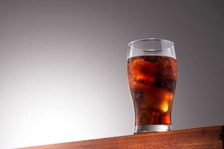 Cola glass with ice cubes on a Wooden Surface With Gradient Background 版權商用圖片