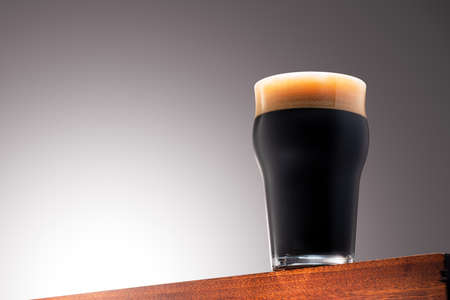 Close up photo of a Glass of dark beer on a Wooden Surface and Gradient Background 版權商用圖片