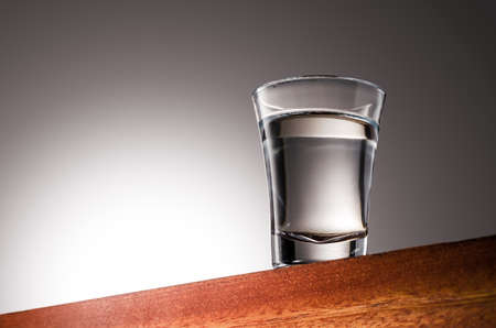 Close up photo of a Tequila Glass Shot Wooden Surface and Gradient Background 版權商用圖片