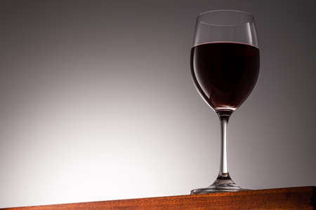 Red wine in a glass on a Wooden Surface and Gradient Background