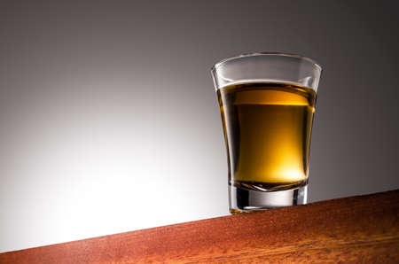 Close up photo of a Gold Tequila Glass Shot Wooden Surface and Gradient Background 版權商用圖片