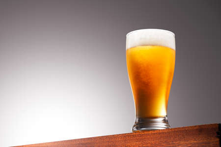 Close up photo of a Glass of beer on a Wooden Surface and Gradient Background