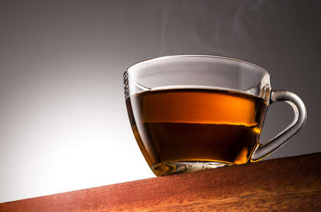 Close up photo of a Glass cup of tea on a Wooden Surface and Gradient Background