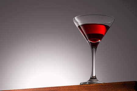 Red Drink in Martini Glass on a Wooden Surface With Gradient Background