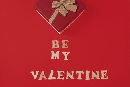 be my valentine phrase made of wooden letters with a gift and an angel on red background top view copy space vertical layout Reklamní fotografie
