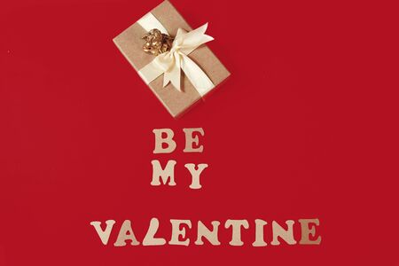 be my valentine phrase made of wooden letters with a gift and an angel on red background top view copy space vertical layout