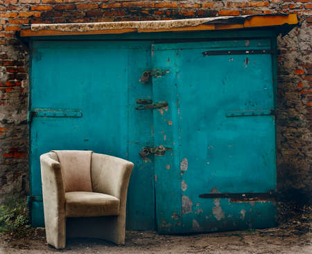 old beige chair in the street at background of blue wall