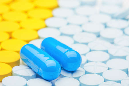 two blue medical pills on the background of colored pills Stock Photo