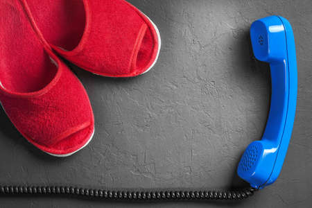 Red slippers with handset on the floor Stock Photo