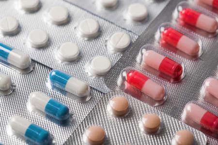 ovalo: Pila de tabletas y píldoras médicas en cajas plásticas de plata