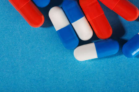 Medical pills white-blue and red on a bright background