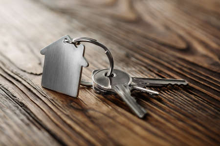 Symbool van huis met zilveren sleutel op houten achtergrond
