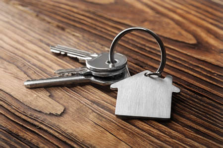 floorboards: House key on  house shaped keychain  on wooden floorboards