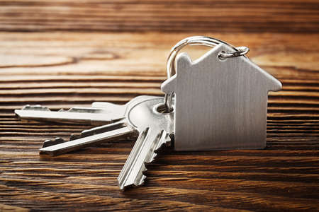 lock symbol: estate concept with symbol of house, key on wooden background Stock Photo
