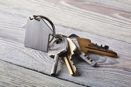 security symbol: estate concept, keychain with house symbol, key on wooden background Stock Photo