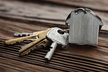 estate concept, keychain with house symbol, key on wooden background Stock Photo